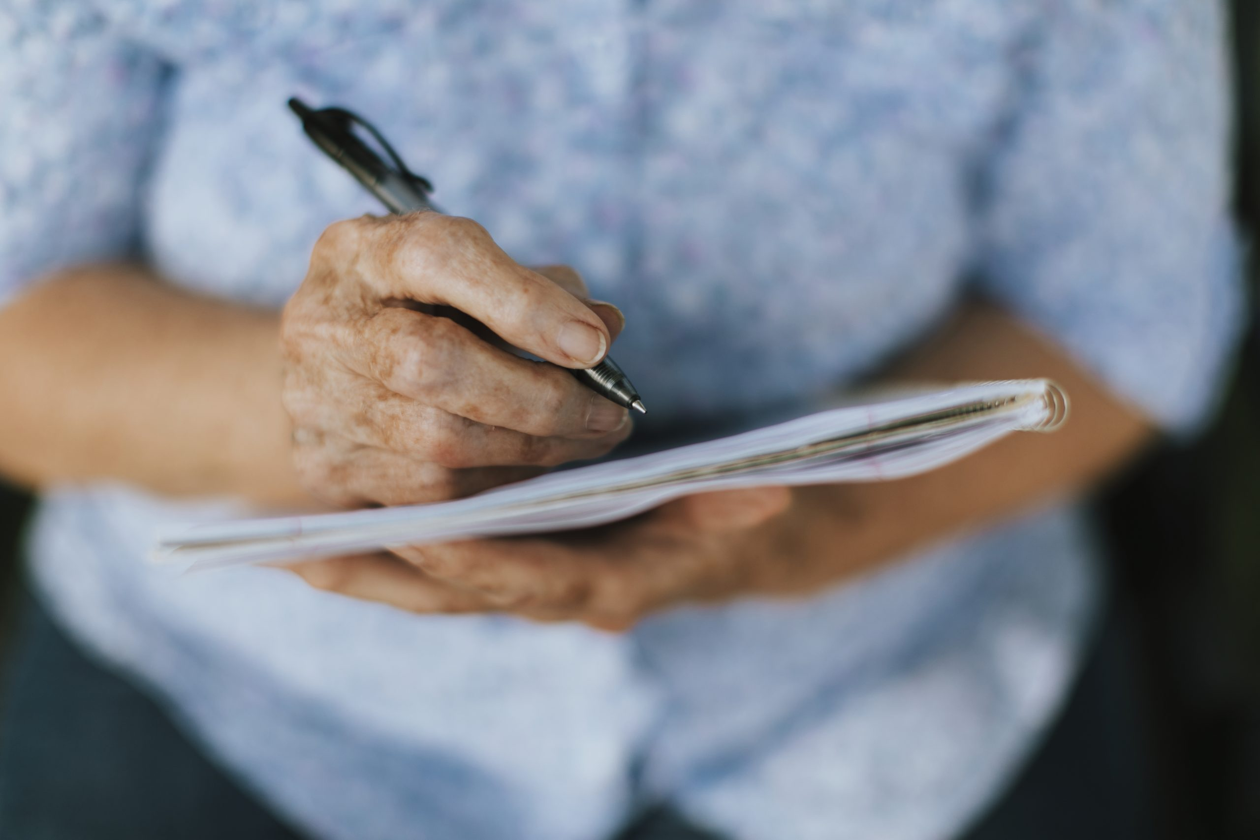 Señora mayor escribe en una libreta